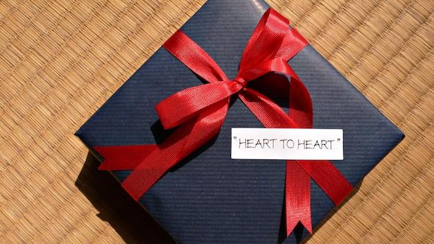 真っ赤な弓と「心から心へ」の言葉でお祝いの贈り物