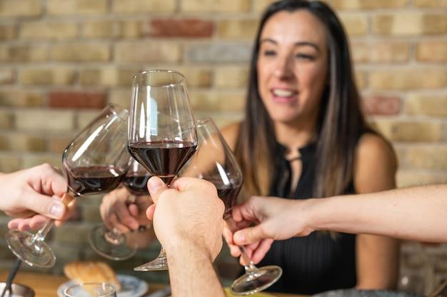 お祝い。乾杯のワイングラスを持っている友人のグループ。