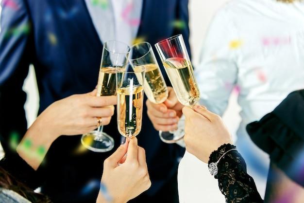 お祝い。乾杯するシャンパンとワインのグラスを持っている手。パーティー、お祝い、アルコール、ライフスタイル、友情、休日、クリスマス、新年、年とチャリンという概念