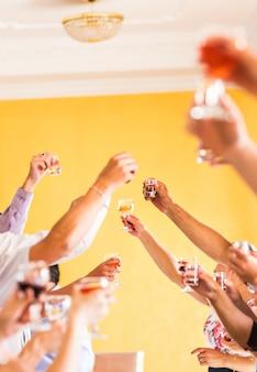 Празднование. руки держат бокалы с шампанским и тостами