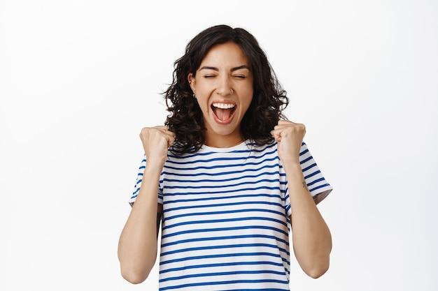 축하. 행복한 브루네트 소녀는 기쁨에서 소리치고, 예라고 말하며, 성공의 승리를 거두고, 목표를 달성하고, 승리를 축하하고, 상을 받고, 흰색 위에 서 있습니다