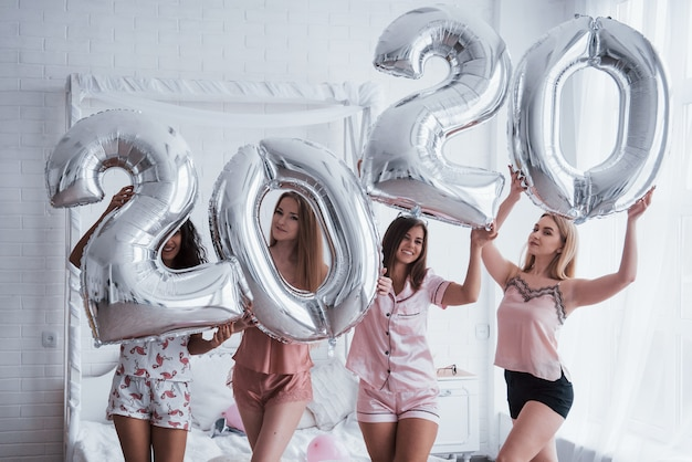 Celebration of holiday. four girls in pink and white clothes stands with silver colored balloons. conception of happy new year