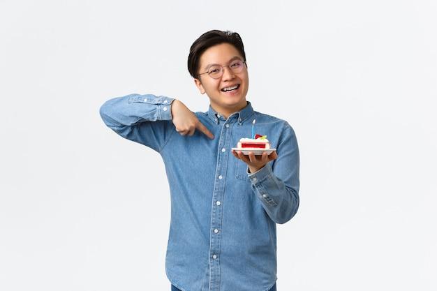 お祝い、休日、ライフスタイルのコンセプト。幸せな驚きの誕生日の男は、b-dayケーキを受け取り、それを指して、喜んで笑って、おいしいデザートを賞賛し、白い背景に立っています。
