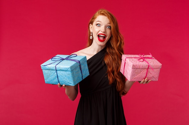お祝い、休日、女性のコンセプトです。 2つの誕生日プレゼント、青とピンクのボックスを保持している驚きと陽気な笑顔の黒のスタイリッシュなドレスで興奮して幸せな女性の赤毛の女性の肖像画