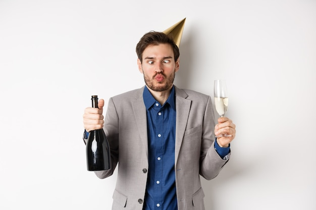 Celebration and holidays concept. funny drunk guy in suit and birthday hat