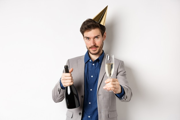 Celebration and holidays concept. handsome man in suit and birthday hat giving glass of champagne
