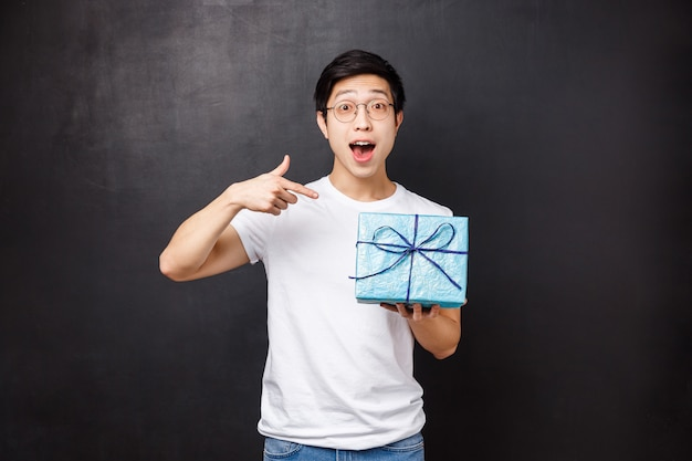 Celebration, holidays and lifestyle concept. portrait of excited and curious cute asian guy asking whats inside gift box, celebrating b-day party holding present and pointing finger at it