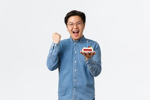 Feste di celebrazione e concetto di stile di vita esultanza uomo asiatico felice che si gode la festa di compleanno tenendo...