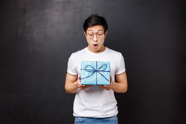 Celebration, holidays and lifestyle concept. surprised and excited, amazed asian guy receive gift box, holding present and looking at it amused didnt expect coworker remembers about birthday
