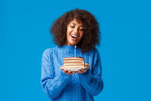 Celebration, holidays and party concept. dreamy and lovely cute african-american woman with afro haircut, in sweater, tilt head and watching at lit candle on birthday cake, smiling making wish