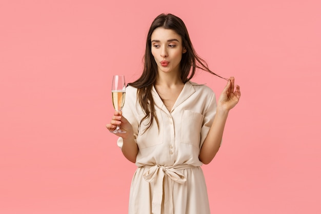 Celebration, holidays and party concept. romantic sensual and coquettish young woman celebrating special occasion, valentines day romantic date, holding glass champagne, folding lip, pink wall