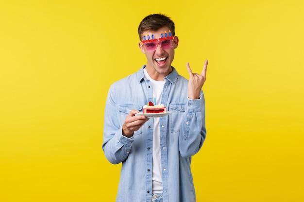 Celebrazione, vacanze e concetto di emozioni della gente. ragazzo biondo felice e spensierato che festeggia il compleanno, si gode la festa, mostra il cartello rock-on e tiene in mano una torta di b-day, sfondo giallo,