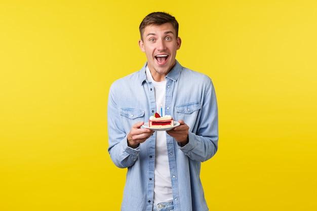 Celebrazione, vacanze e concetto di emozioni della gente. entusiasta uomo felice che tiene piatto con torta di compleanno, celebrando b-day, esprimendo desiderio e soffiando una candela accesa, sorridendo eccitato, sfondo giallo.