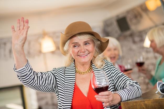 축하. 와인 한 잔을 들고 갈색 모자에 즐거운 여자