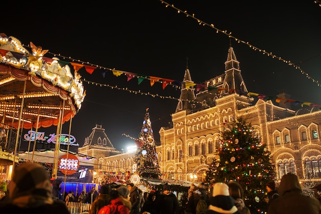Celebration lights and decorations on red square for festive christmas and new year. shining yellow lights on facade gum in moscow, russia. night cityscape of moscow