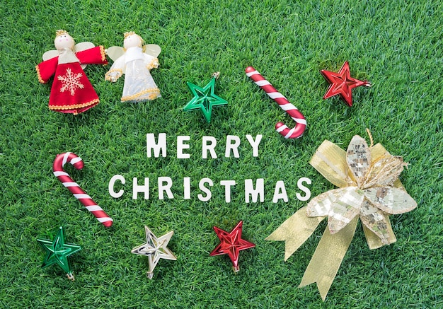 Celebration of new year and christmas, top view christmas alphabet and decoration on green grass background