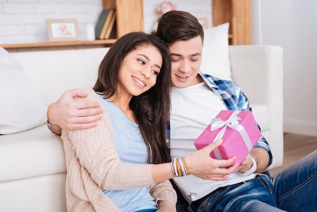 愛のお祝い。男性が女性を抱きしめている間プレゼントを保持している甘い陽気なカップル