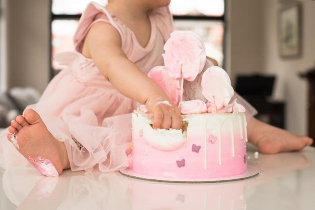 소녀의 첫 번째 생일 축하, 스펀지 케이크, 깨진 마쉬 멜로우, 아기 손 및 시차. 허용, 불순종, 손으로 먹는 것