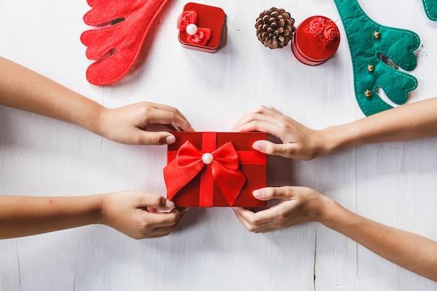 カラフルな紙吹雪、白い色の背景にペーパーアートでギフトボックスの装飾を与える若い人の手でお祝いパーティーやクリスマスの日のコンセプトのアイデア