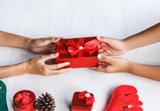 ギフトボックスを与える若い人の手でお祝いパーティーやクリスマスの日のコンセプトのアイデア