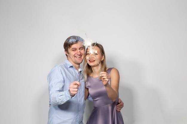 축하, 파티, 휴일 개념 - 행복한 남자와 여자가 폭죽을 들고 회색 배경 위에 껴안고 있습니다.