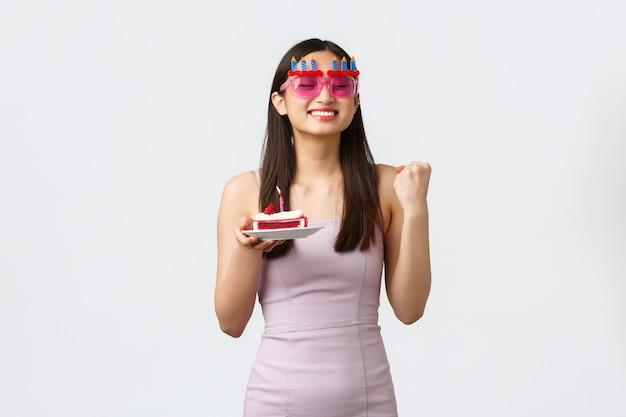 お祝い、パーティー、休日のコンセプト。面白いメガネとドレス、応援で陽気なかわいい希望に満ちたアジアの女の子