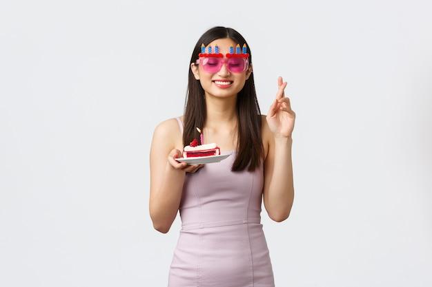 Концепция празднования, вечеринки и праздников. мечтательная обнадеживающая азиатская именинница в платье, скрестив пальцы, желает закрытых глаз и улыбки