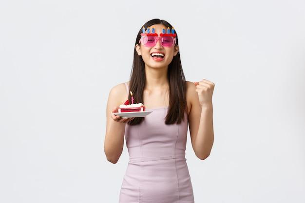 お祝い、パーティー、休日のコンセプト。面白い眼鏡とドレス、勝利の拳ポンプで楽観的な幸せな美しいアジアの女の子