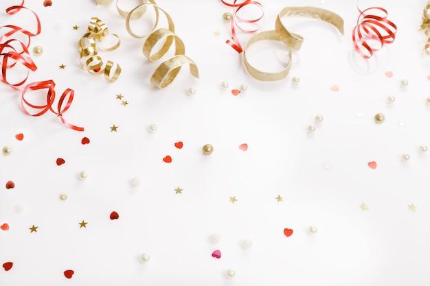 축하, 파티 배경 개념에는 황금색과 빨간색 색종이 조각, 깃발이 있습니다. 생일, 새해, 크리스마스 컨셉입니다. 오버 헤드 평면도, 평면 누워. 공간을 복사합니다.