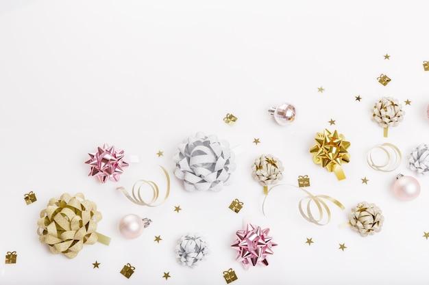 Празднование, идеи для вечеринок с золотыми, серебряными и розовыми красочными подарочными бантами, конфетти, растяжками. день рождения, новый год, рождество концепции. вид сверху, плоская планировка. скопируйте пространство.