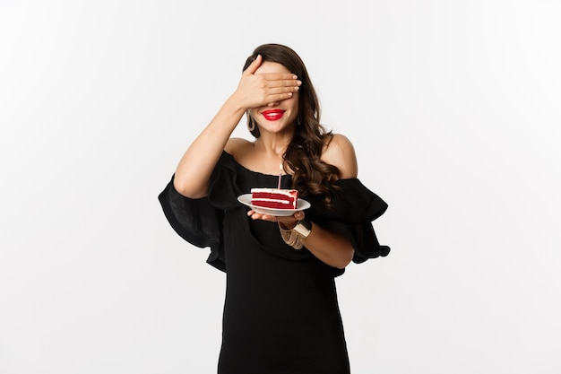 Celebration and party concept. happy birthday girl in black dress, red lipstick, close eyes and making wish on b-day cake, standing over white background.