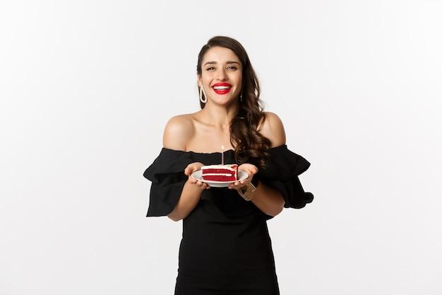Celebrazione e concetto di festa. felice splendida donna che ha compleanno, che tiene la torta di b-day e sorridente, esprimere il desiderio, in piedi in abito nero con il trucco.