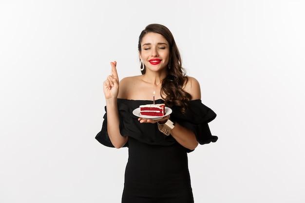 Celebrazione e concetto di festa. donna speranzosa e sognante che esprime desiderio sulla torta di compleanno, incrociare le dita e sorridere felice, in piedi su sfondo bianco.