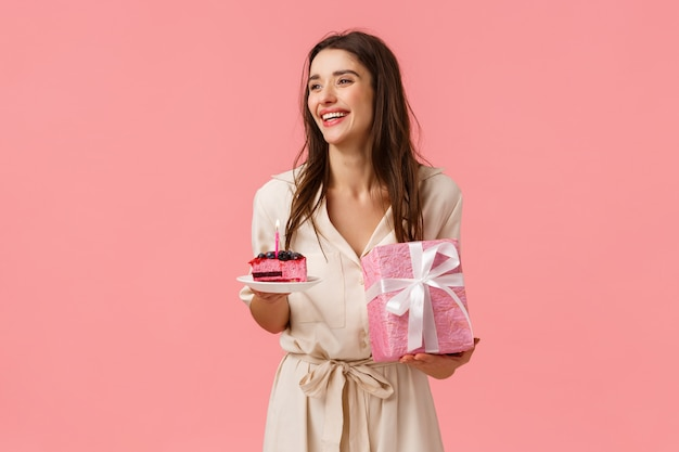 Celebration, party and happiness concept. carefree smiling happy european woman having fun parying own b-day party, holding gift and piece cake, blow-out candle, pink wall
