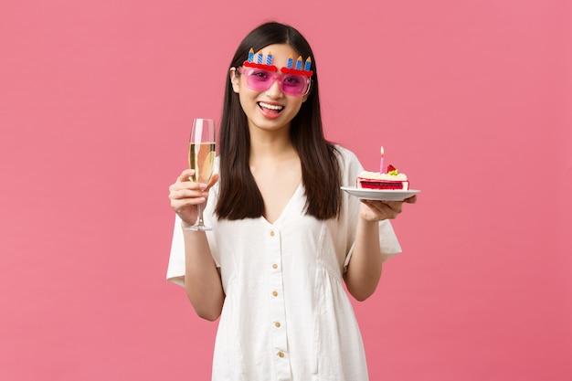 축하, 파티 휴일 및 재미있는 개념입니다. 유쾌한 행복한 아시아 여성이 재미있는 선글라스를 쓰고 생일을 축하하고 유리 샴페인과 촛불이 켜진 b-day 케이크를 들고 소원을 빌었습니다.