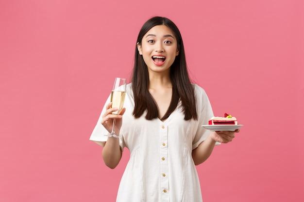 Празднование, партийные праздники и забавная концепция. мечтательная красивая женщина празднует свой день рождения с бокалом шампанского и тортом на день рождения, выглядит удивленным и взволнованным, стоя на розовом фоне.