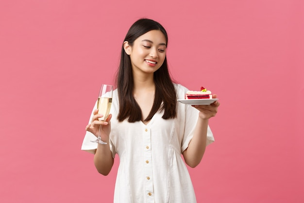 축하, 파티 휴일 및 재미있는 개념입니다. 유리 샴페인과 b-day 케이크로 생일을 축하하는 꿈꾸는 아름다운 여성, 디저트에서 평온한 미소, 분홍색 배경에 서 있습니다.