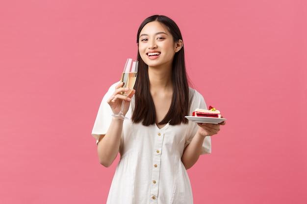 축하, 파티 휴일 및 재미있는 개념입니다. 생일을 축하하는 행복한 아시아 여성은 맛있는 비데이 케이크와 샴페인을 마시며 카메라를 즐겁게 하고 분홍색 배경을 바라보며 웃고 있습니다.