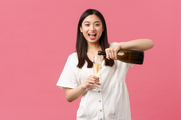 Празднование, партийные праздники и забавная концепция. счастливая беззаботная азиатская женщина в отпуске, наливает шампанское в бокал и смеется, наслаждаясь выходными или отдыхом, стоя на розовом фоне.