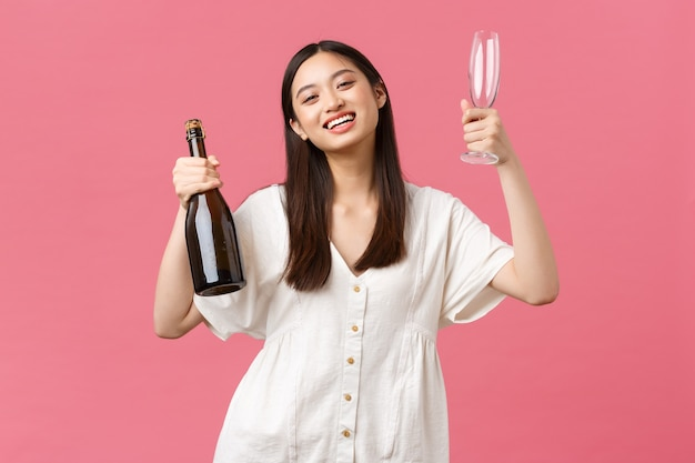 Празднование, партийные праздники и забавная концепция. радостная счастливая азиатская девушка готова насладиться выходным днем с подругами, принести шампанское и бокалы, улыбаясь в камеру, стоя на оптимистичном розовом фоне.