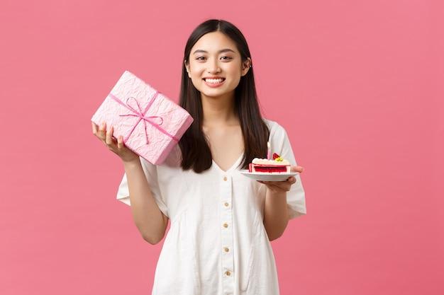 축하 파티 휴일 및 재미있는 개념 생일 홀을 축하하는 흰색 드레스를 입은 사랑스러운 아시아 소녀...