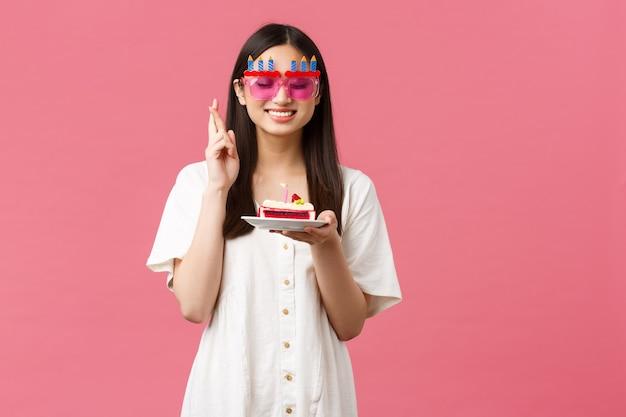 축하, 파티 휴일 및 재미있는 개념입니다. 웃는 생일 소녀는 b-day 케이크에 소원을 빌고, 눈을 감고, 행운을 빕니다, 꿈이 이루어지기를 원하고, 분홍색 배경입니다.