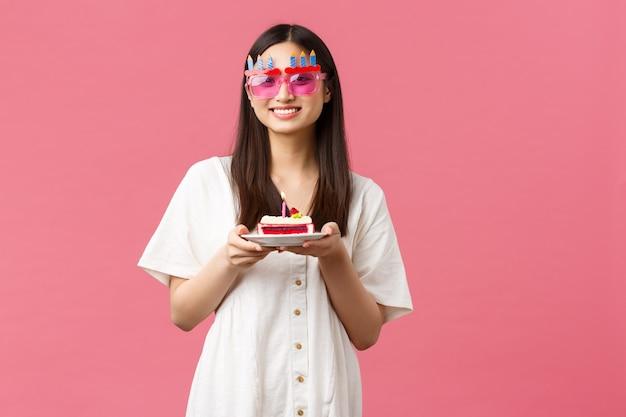 축하, 파티 휴일 및 재미있는 개념입니다. 재미있는 선글라스를 끼고 웃고 있는 귀여운 한국 소녀가 생일 케이크를 들고, 축하 행사를 즐기고, 분홍색 배경에 밝은 분위기로 서 있습니다.