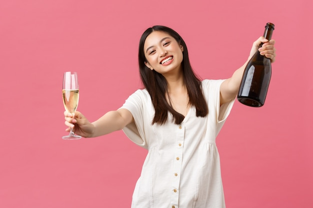 Celebration, party holidays and fun concept. happy smiling asian woman host of event, holding bottle champagne and glass and reaching hands for hugging guest, standing pink wall