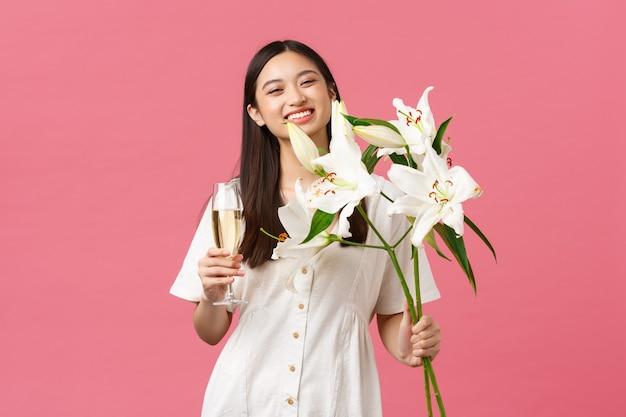 Celebrazione, feste di festa e concetto di divertimento. sciocco buon compleanno ragazza in abito bianco, sorridente ampiamente come ricevere bellissimo mazzo di gigli, tenendo in mano un bicchiere di champagne, in piedi sfondo rosa