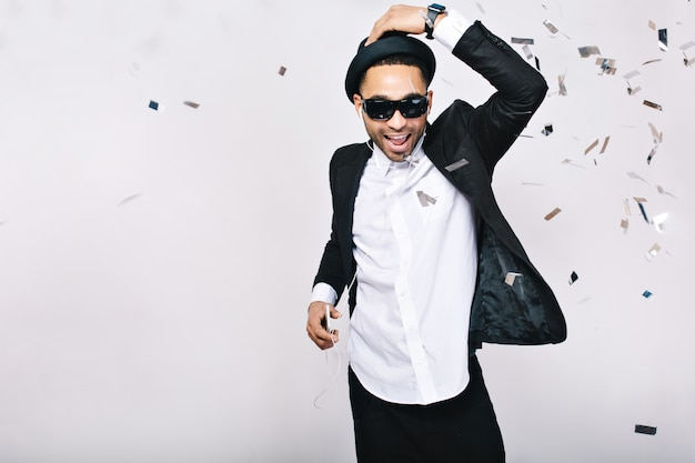 Celebration, party time, happy weekends of excited handsome guy in suit, hat, black sunglasses having fun in tinsels. fashionable look, listening to music, dancer.