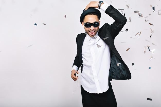 お祝い、パーティーの時間、スーツ、帽子、ティンセルで楽しんでいる黒いサングラスで興奮しているハンサムな男の幸せな週末。ファッショナブルな外観、音楽を聴く、ダンサー。