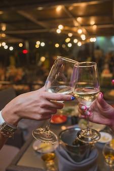 お祝い。乾杯する白ワインのグラスを持っている人。