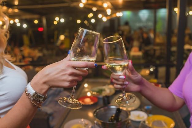 Celebration. people holding glasses of white wine making a toast.