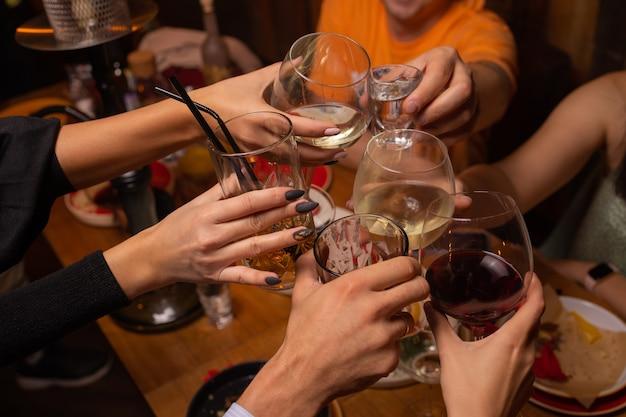 Celebration people holding glasses of white wine making a toast